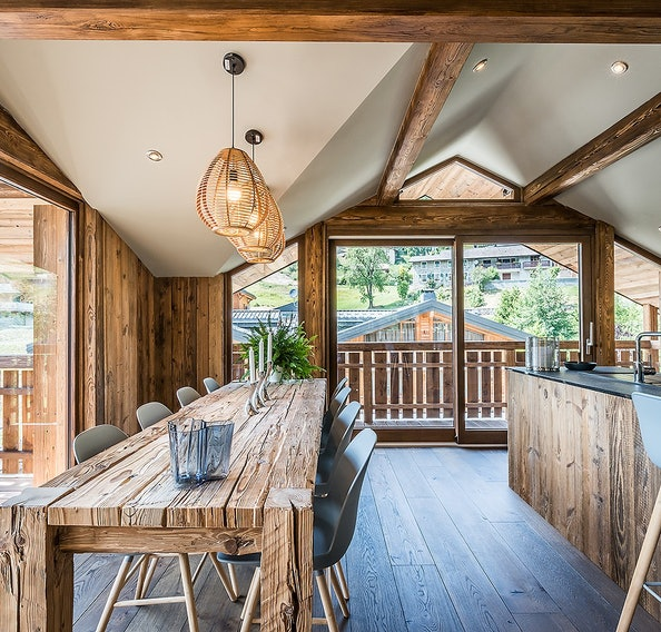 Large wood dining table with open kitchen at Moulin III luxury chalet in Les Gets