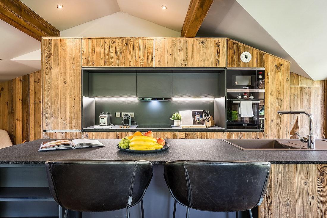 Cuisine ouverte noire et en bois massif dans le chalet Moulin I Les Gets