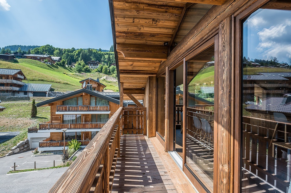 Large wooden terrace with mountain views at Moulin III luxury chalet in Les Gets