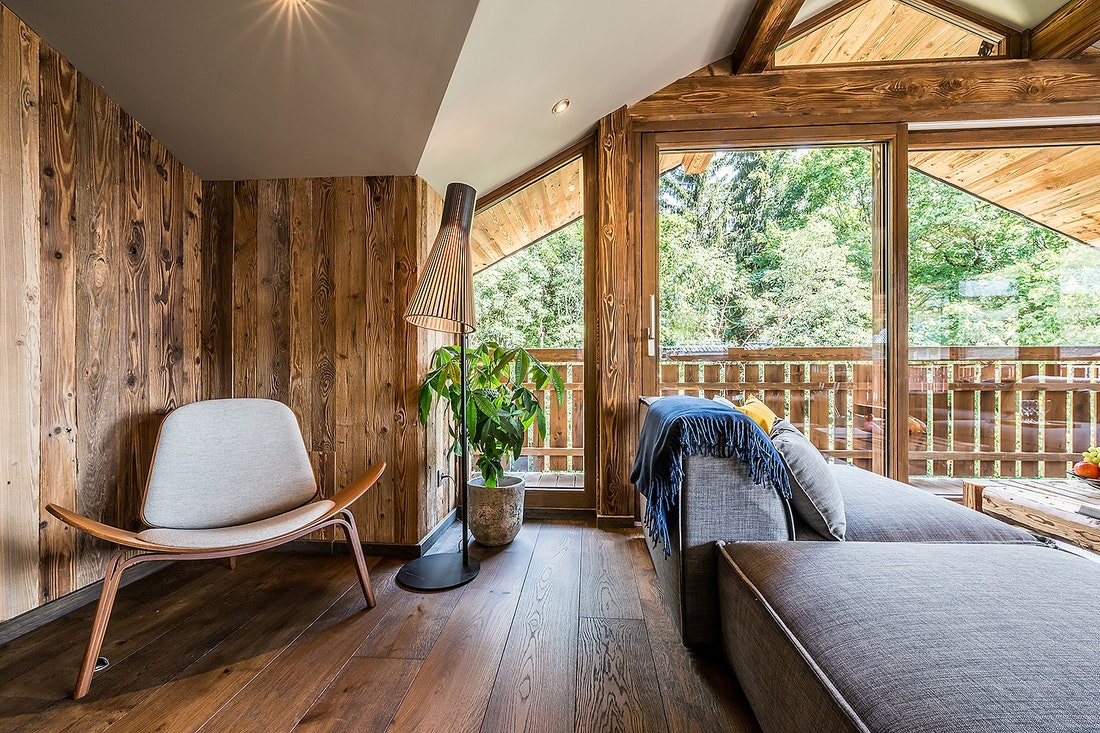 Wooden living room with reading chair at Moulin III luxury chalet in Les Gets