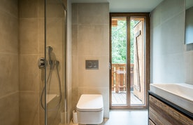 Modern light grey bathroom with shower at Moulin III luxury chalet in Les Gets