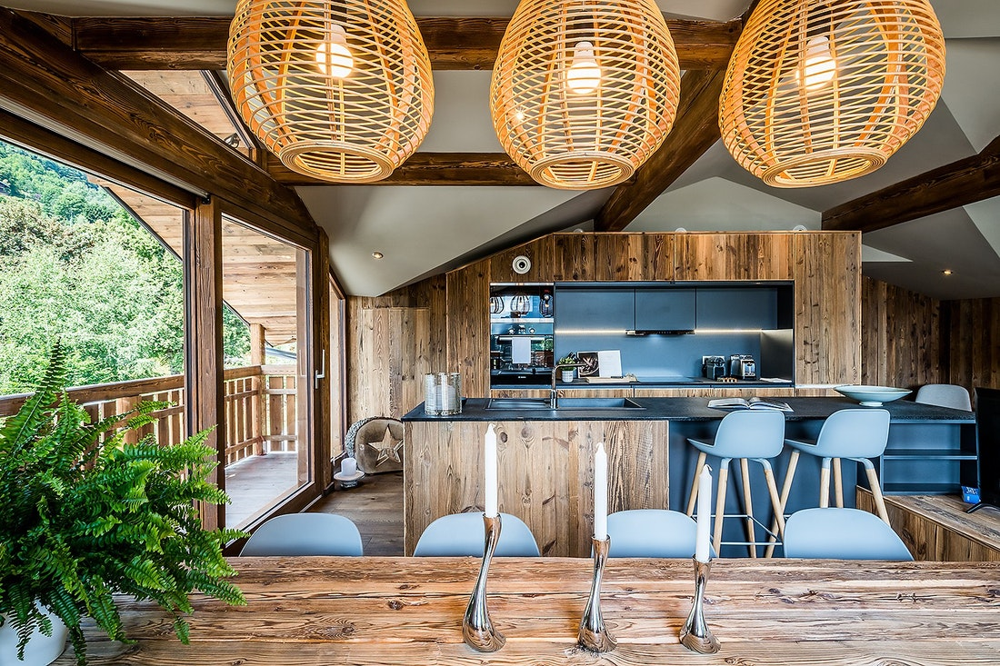 Black and wood open kitchen with large windows at Moulin III luxury chalet in Les Gets