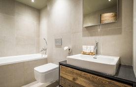 Light grey modern bathroom with bathtub at Moulin I luxury chalet in Les Gets