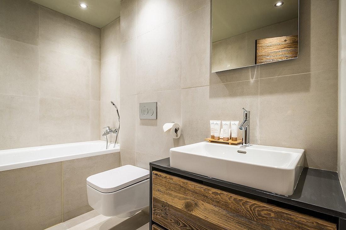 Salle de bain gris clair avec baignoire dans le chalet Moulin I Les Gets