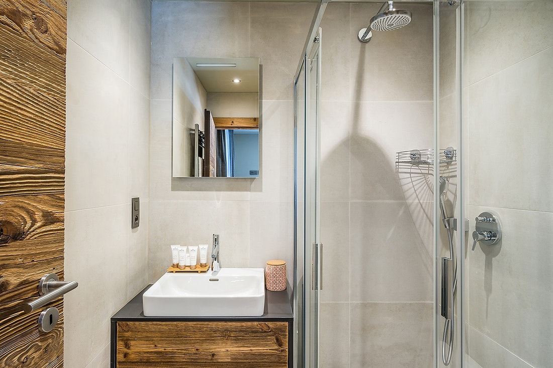 Modern beige and wooden bathroom with shower at Moulin III luxury chalet in Les Gets