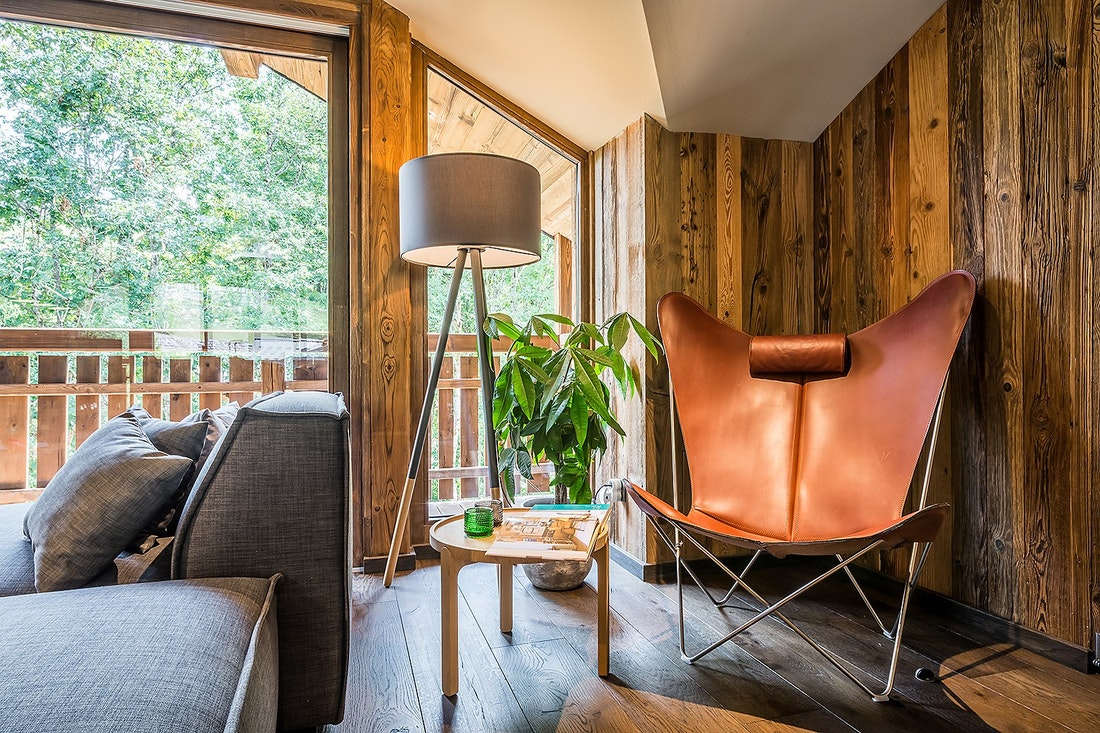 Brown leather armchair with a wooden side table at Moulin II luxury chalet in Les Gets