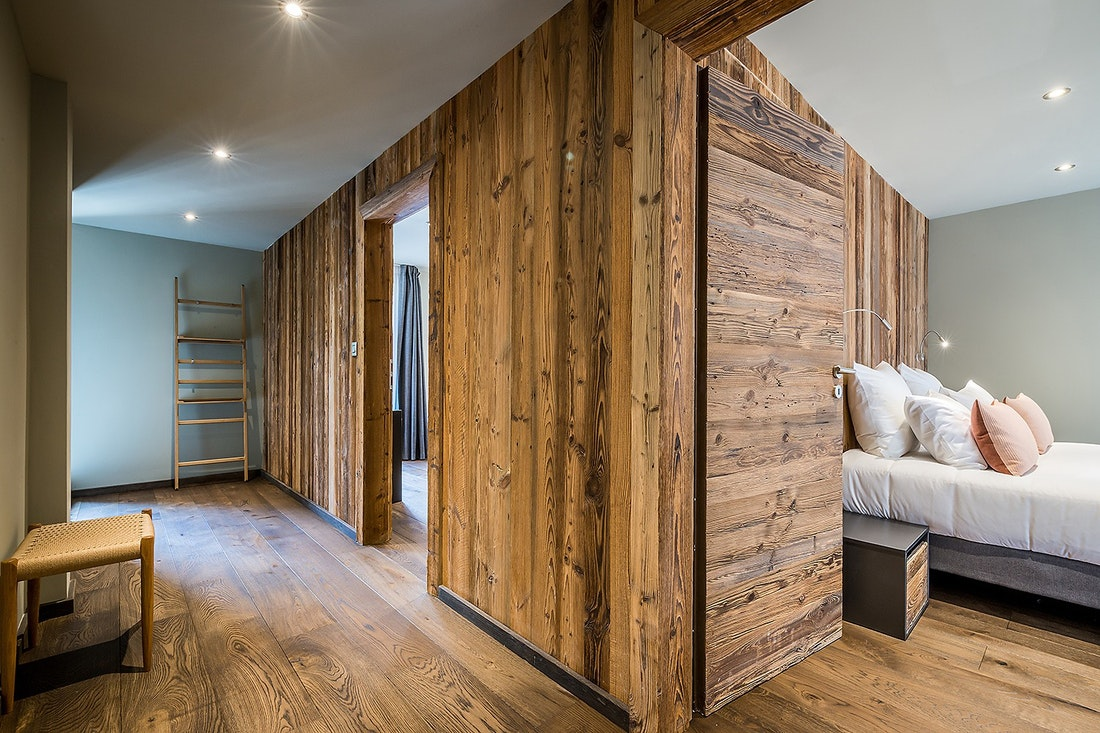 Wooden corridor with view over a double bedroom of Moulin II luxury chalet in Les Gets