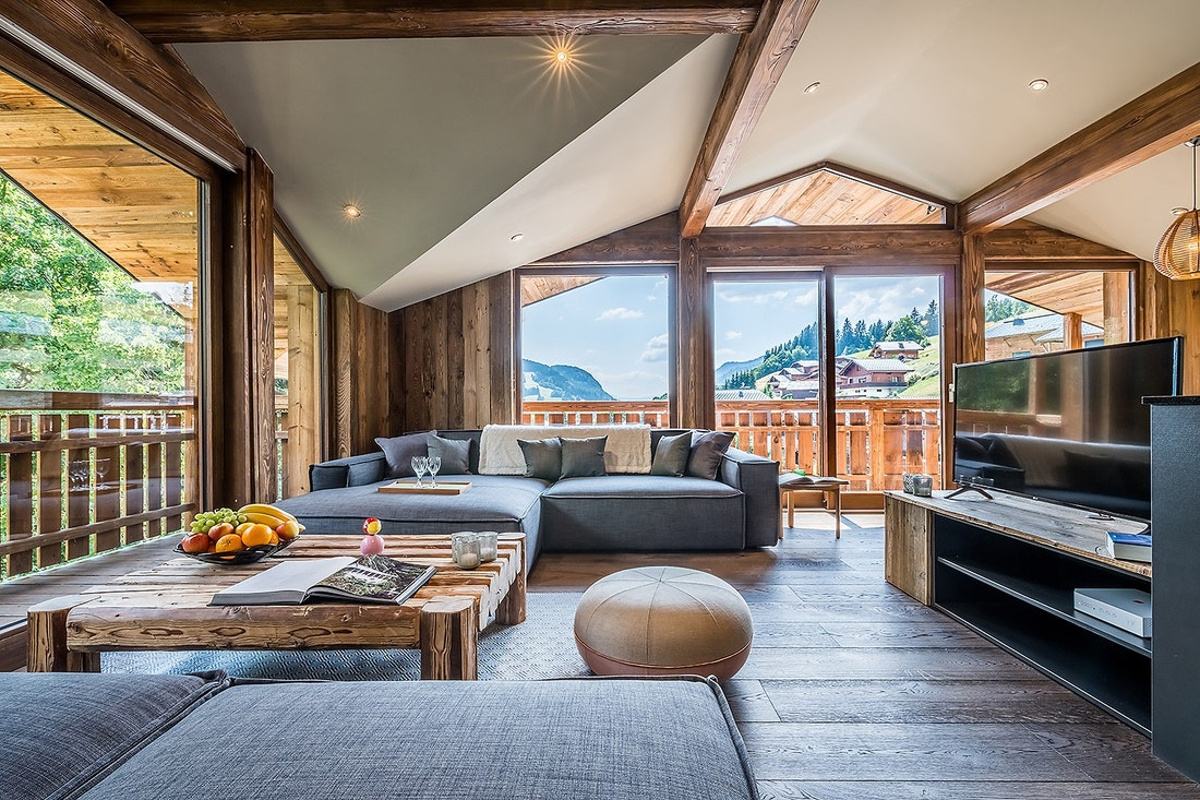 Wooden living room with grey couches at Moulin III luxury chalet in Les Gets