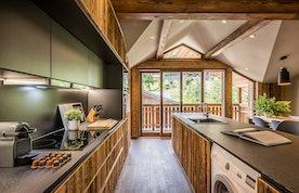 Black and wood kitchen featuring a Nespresso coffee machine