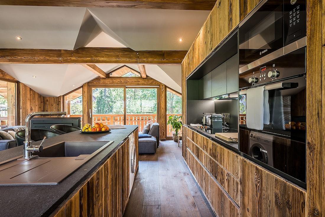 Cuisine ouverte équipée en bois dans le chalet Moulin I Les Gets