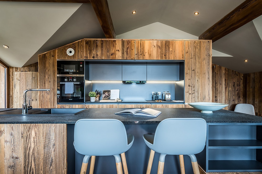 Black and wood open kitchen with bar stools at Moulin III luxury chalet in Les Gets