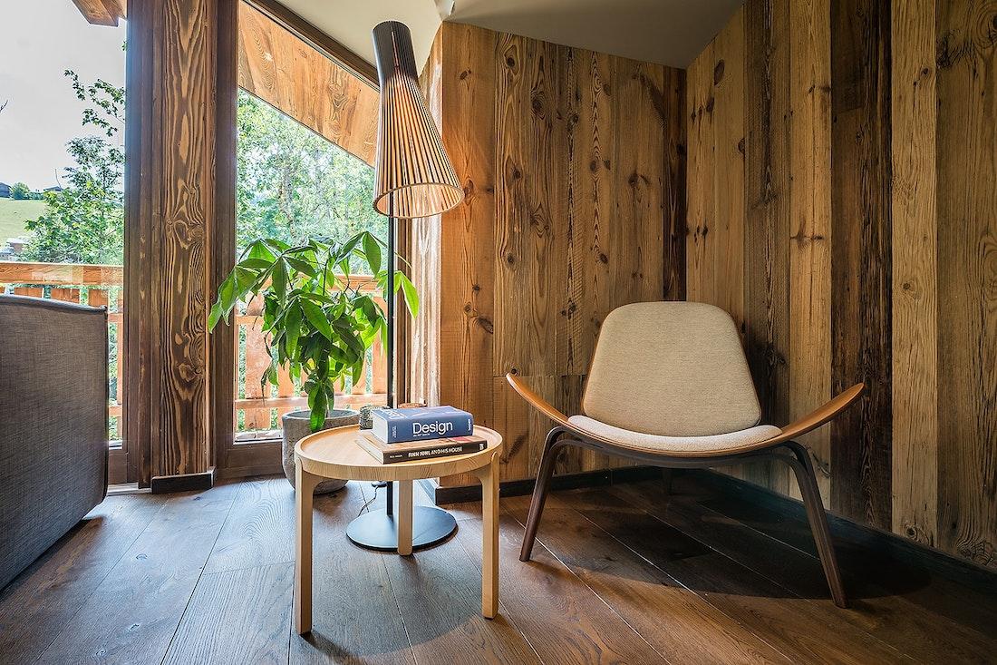 Coin lecture avec chaise et table basse en bois dans le chalet Moulin I Les Gets