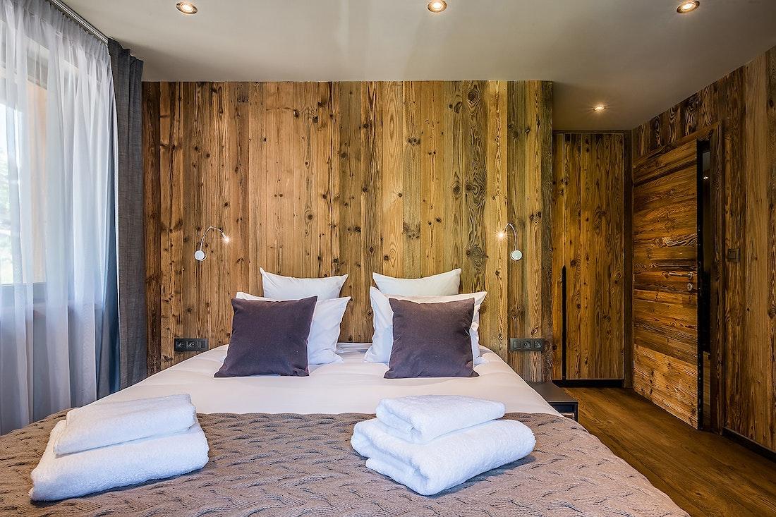 Chambre double en suite avec murs en bois dans le chalet Moulin I Les Gets