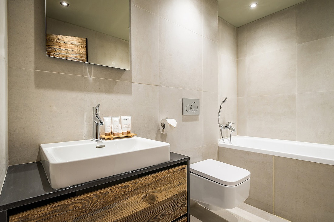 Modern beige and wooden bathroom with bathtub at Moulin III luxury chalet in Les Gets
