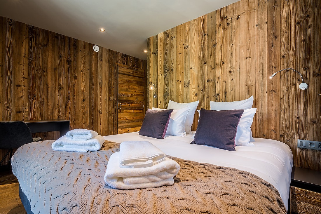 Cosy double bedroom with wooden walls at Moulin III luxury chalet in Les Gets