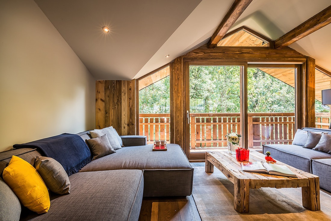 Wooden living room with a grey couch at Moulin II luxury chalet in Les Gets