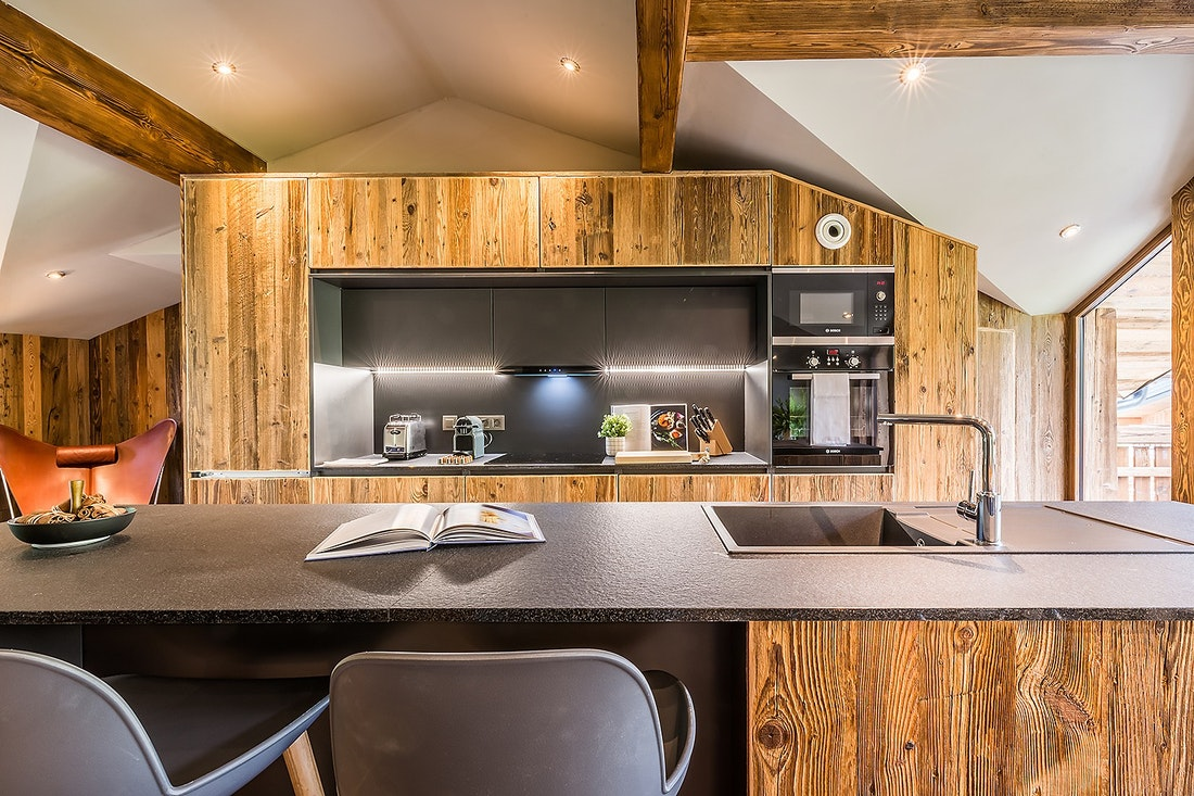 Black and wood open kitchen with a bar at Moulin II luxury chalet in Les Gets