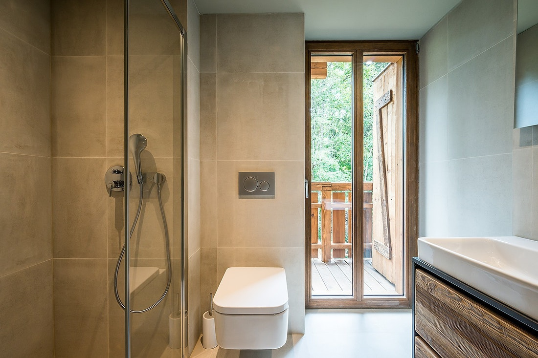 Grey modern bathroom with shower at Moulin II luxury chalet in Les Gets
