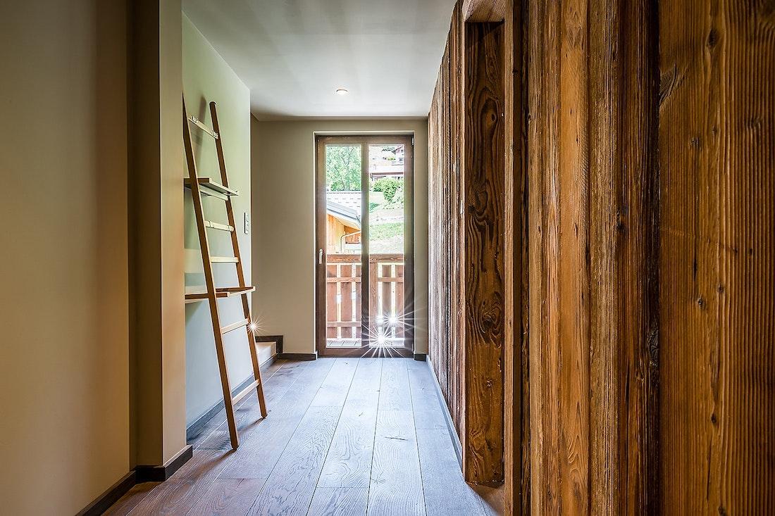 Couloir en bois avec échelle décorative dans le chalet Moulin I Les Gets