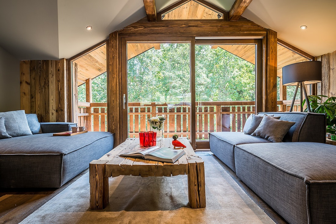 Wooden living room with large windows at Moulin II luxury chalet in Les Gets