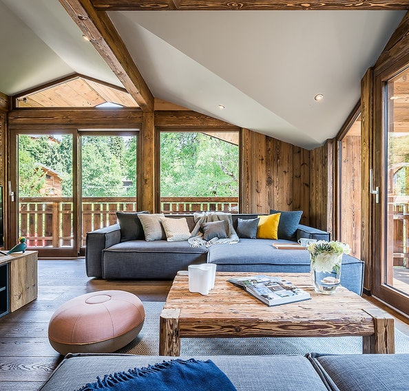 Wooden living room with grey couches at Moulin I luxury chalet in Les Gets