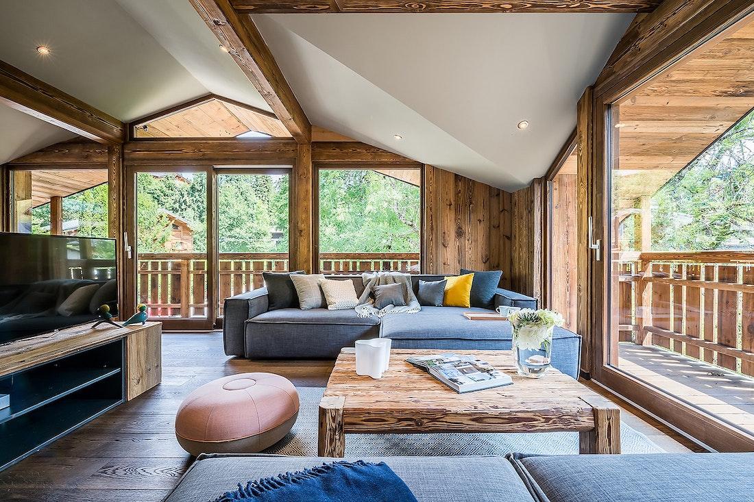 Salon en bois avec télévision et canapés gris dans le chalet Moulin I Les Gets