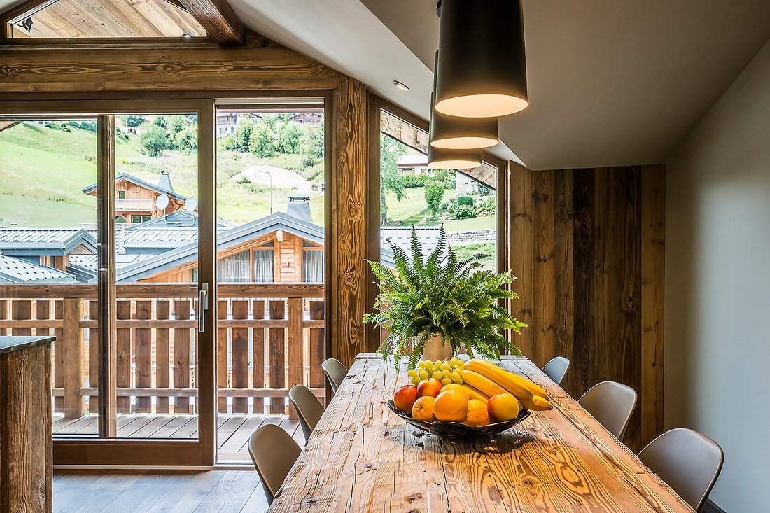 Large wood table with a fruit basket in the kitchen of Moulin II luxury chalet in Les Gets