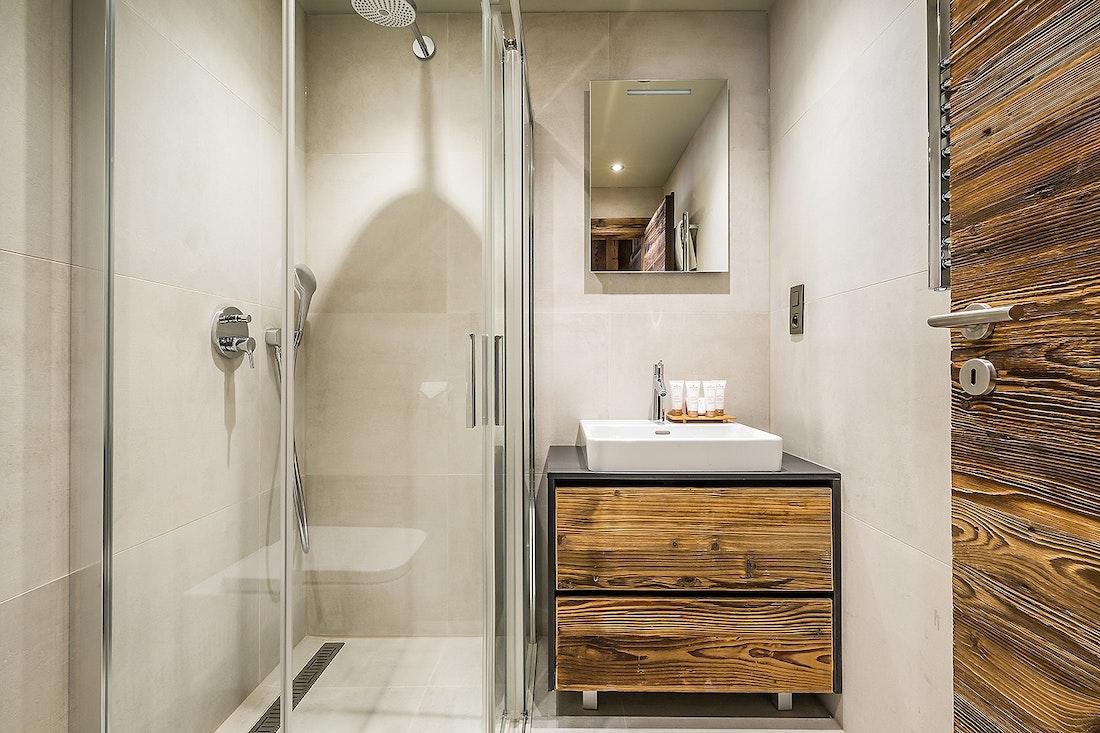 Salle de bain gris clair avec meubles en bois dans le chalet Moulin I Les Gets