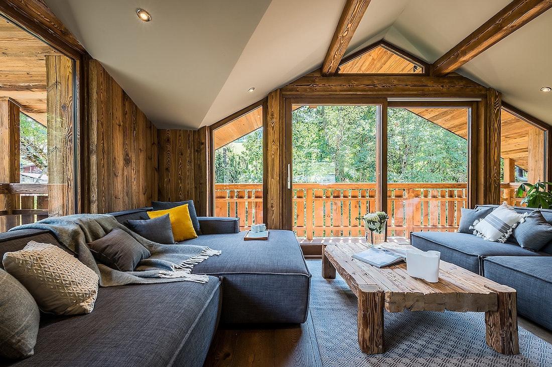 Salon en bois avec grand canapé gris bleu dans le chalet Moulin I Les Gets