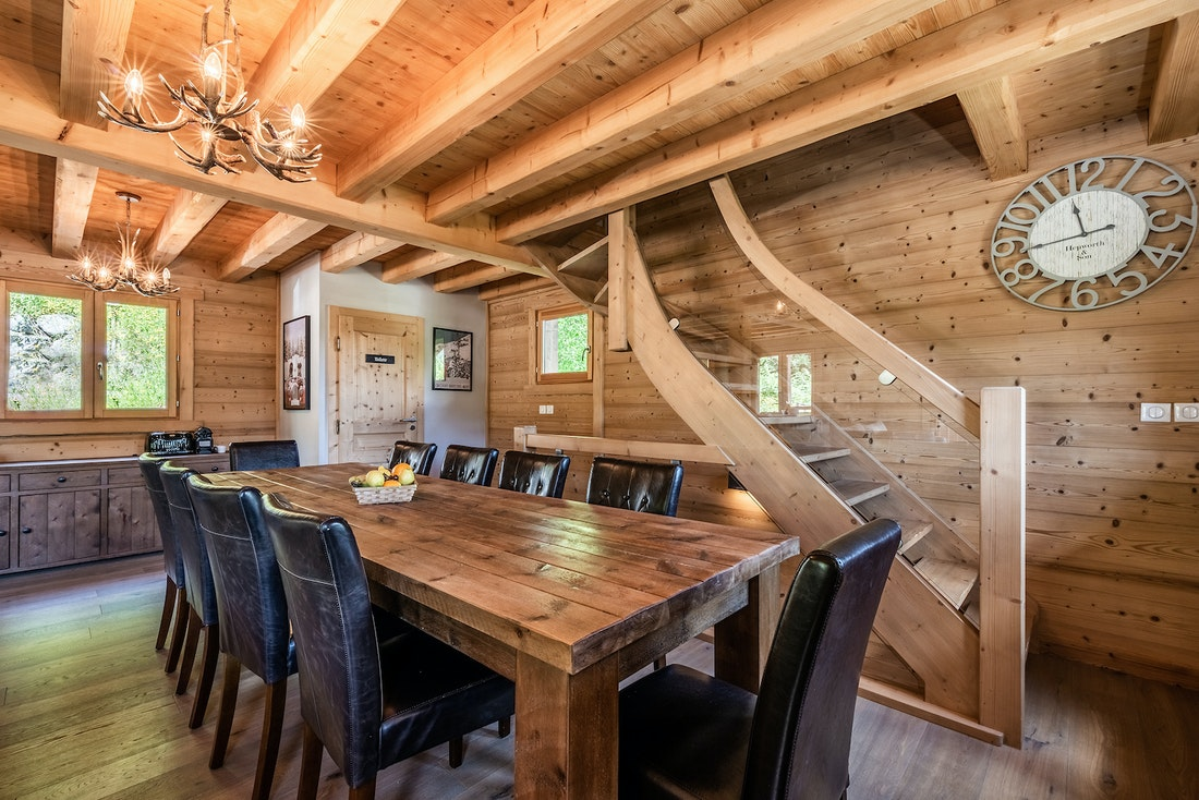 Dining room with wooden walls and black leather chairs at Balata luxury chalet in Morzine