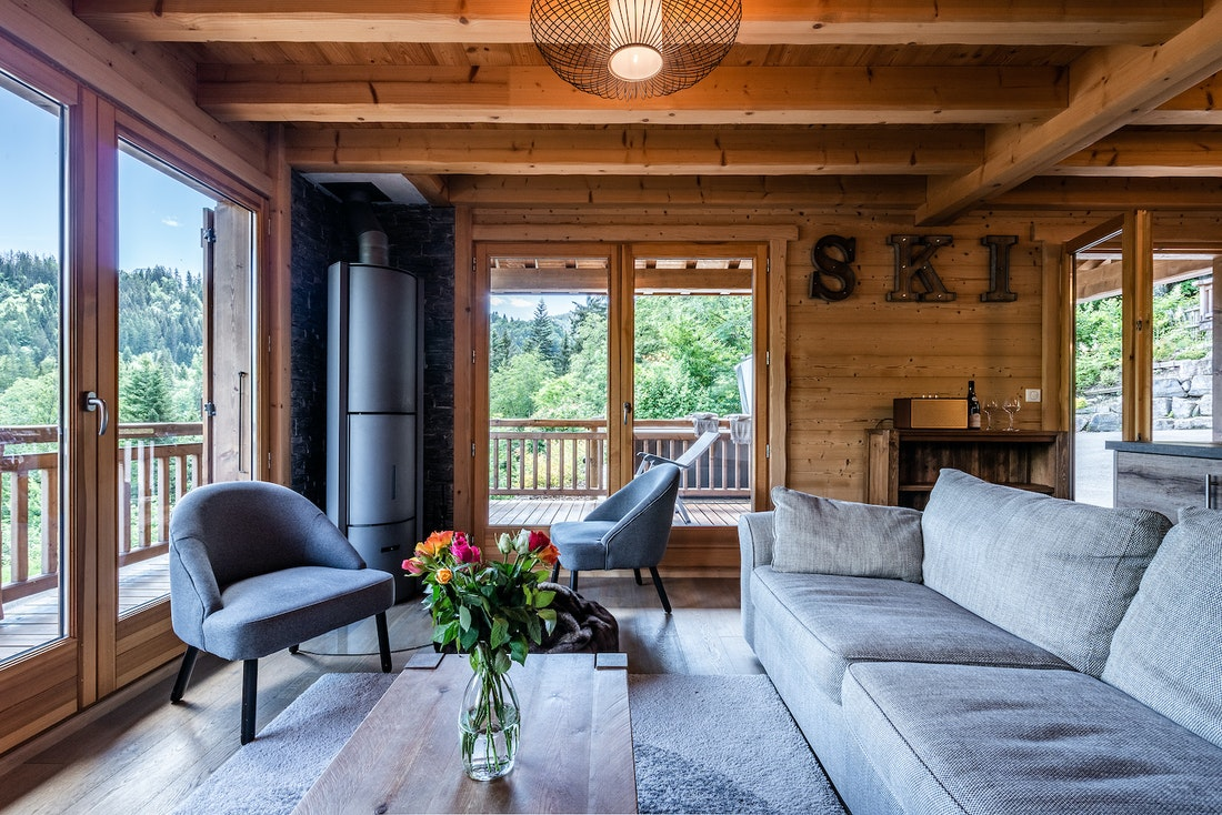 Modern living room with two armchairs and a grey sofa overlooking the forest at Balata luxury chalet in Morzine