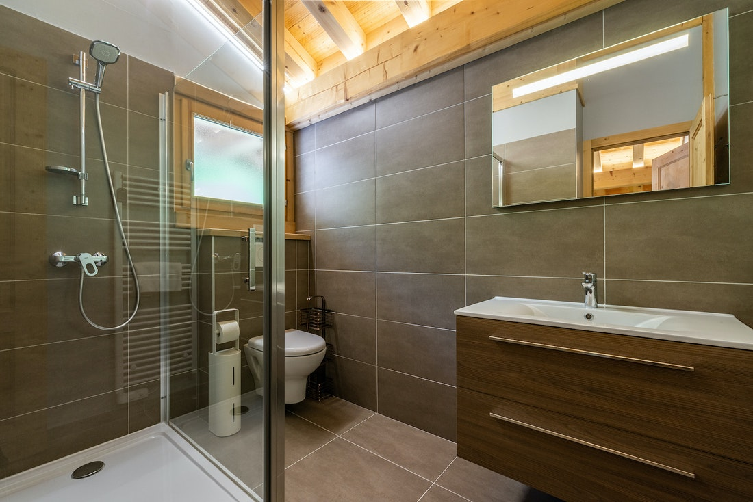 Modern grey bathroom with shower and toilet at Balata luxury chalet in Morzine