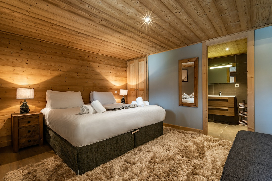 Ensuite bedroom with beige faux-fur carpet and bear shaped bedside tables at Balata luxury chalet in Morzine