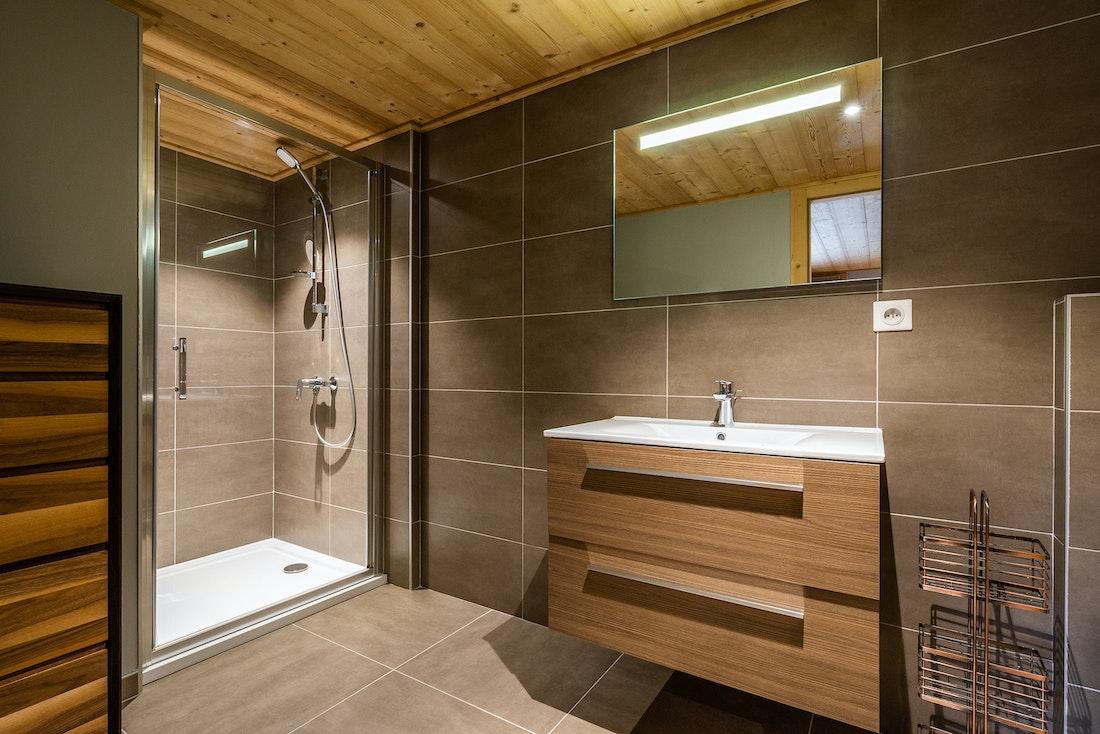 Modern bathroom with dark grey shower and wooden sink at Balata luxury chalet in Morzine