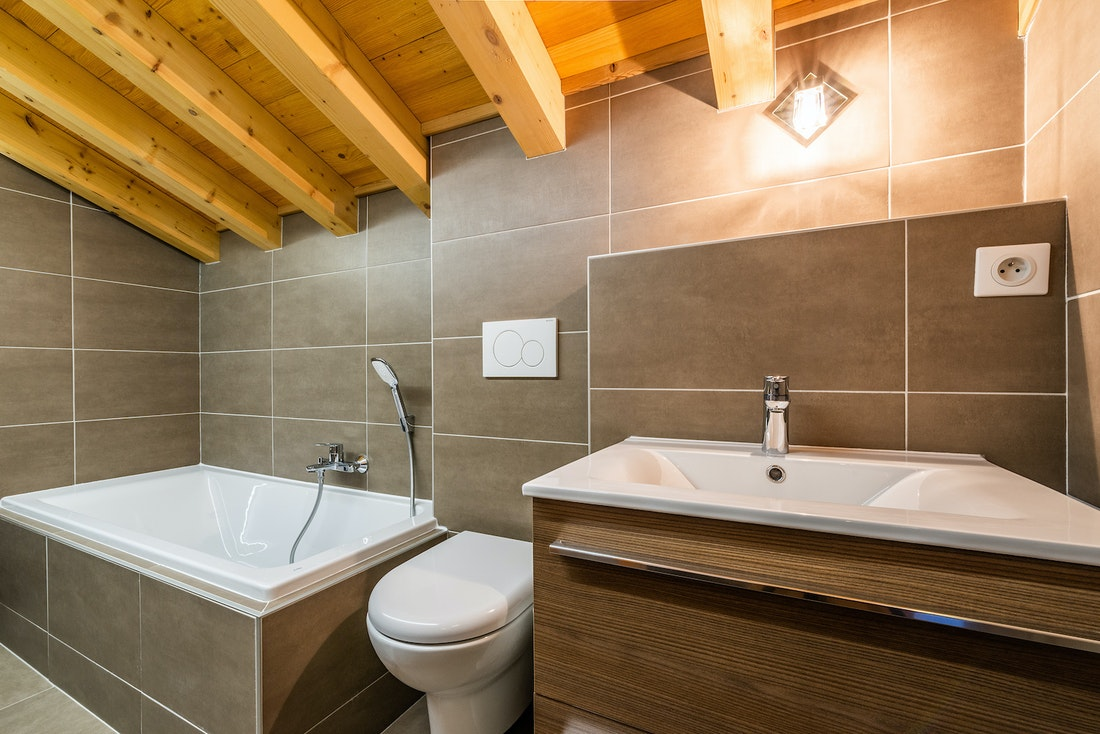Modern bathroom with bathtub and wooden sink at Balata luxury chalet in Morzine