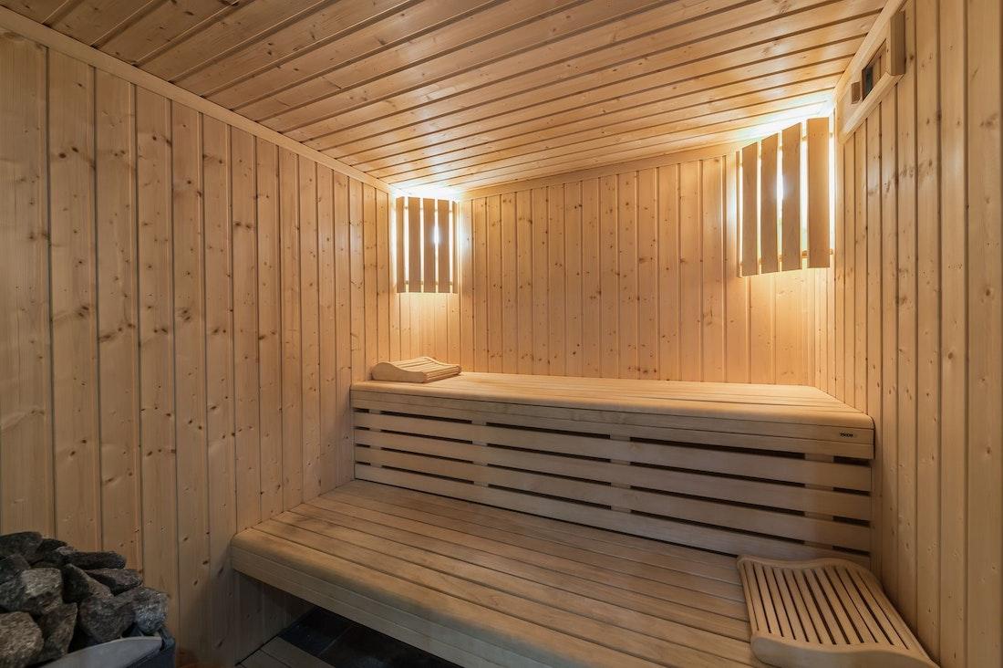 Sauna de luxe aux pierres chaudes dans l'espace bien-être de l'appartement Moabi Courchevel Le Praz avec accès skis aux pieds