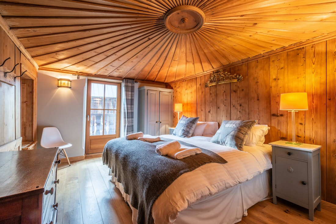 Double bedroom en-suite with carved wooden ceiling at La Ferme de Margot luxury chalet in Morzine