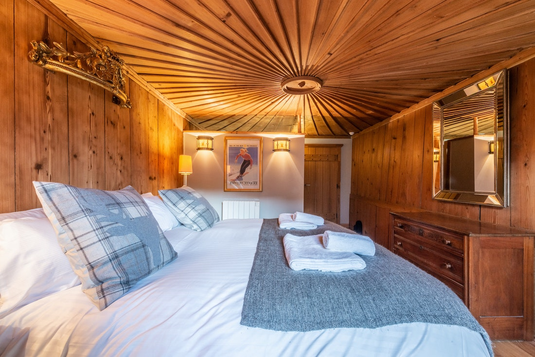 Double bedroom with carved wooden ceiling at La Ferme de Margot luxury chalet in Morzine