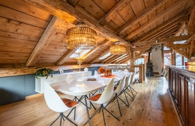 Modern dining room with a white table and orange chairs at La Ferme de Margot luxury chalet in Morzine