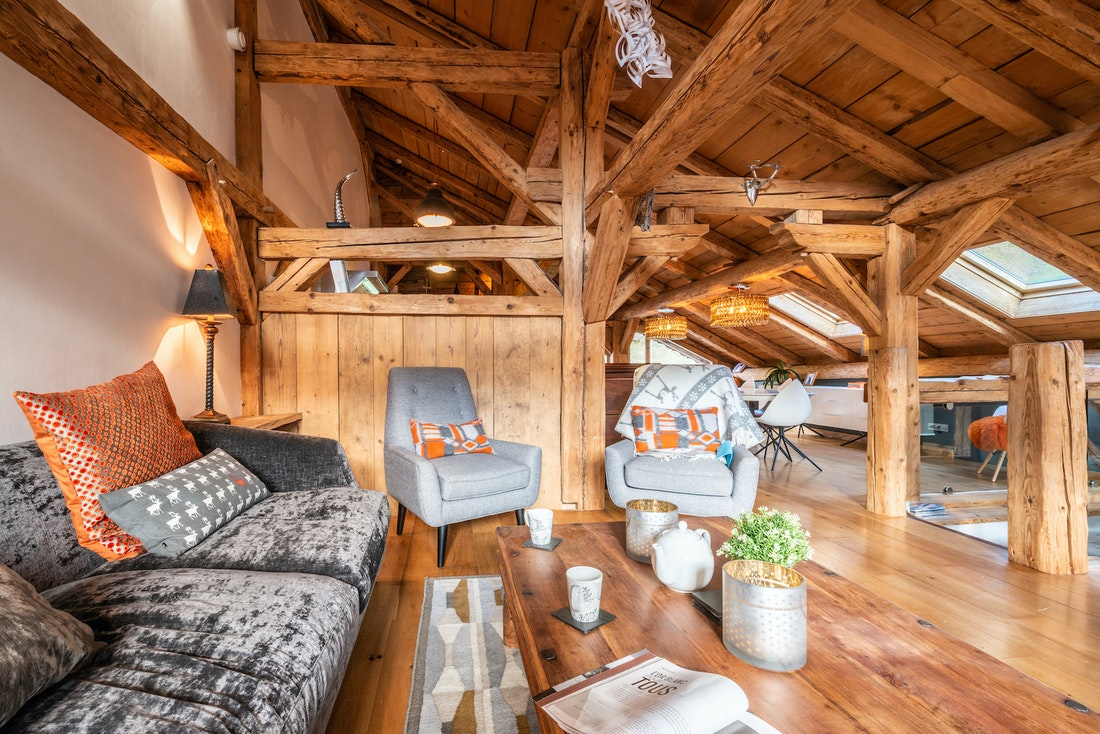 Living room with grey couches and armchair at La Ferme de Margot luxury chalet in Morzine