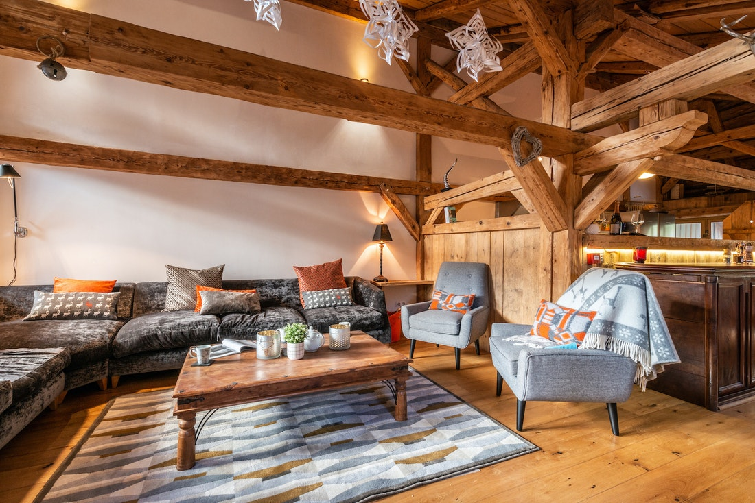 Living room with dark grey couches and modern carpet at La Ferme de Margot luxury chalet in Morzine