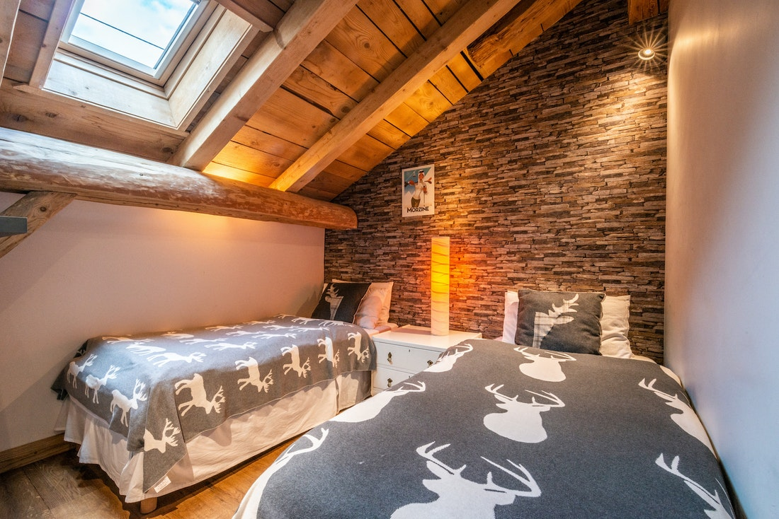 Two single beds with reindeer-themed sheets at La Ferme de Margot luxury chalet in Morzine