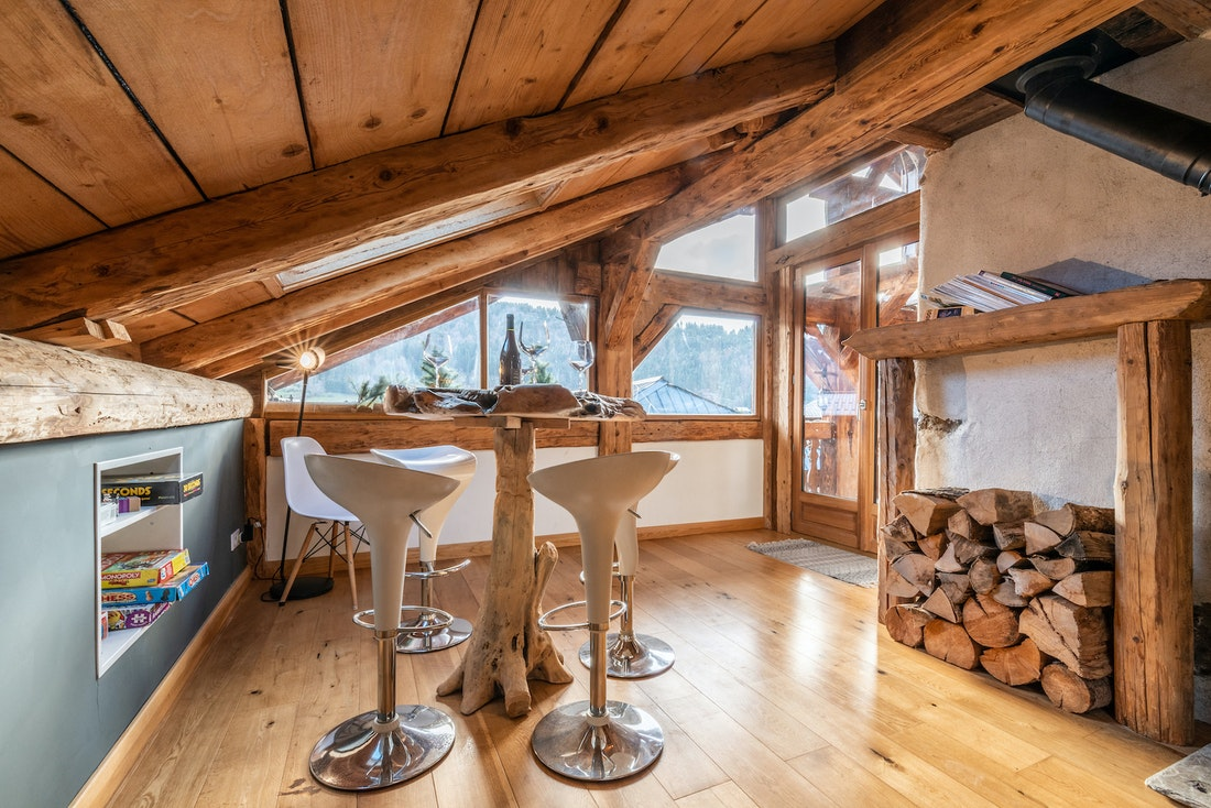 Wooden high-top table and white chairs at La Ferme de Margot luxury chalet in Morzine