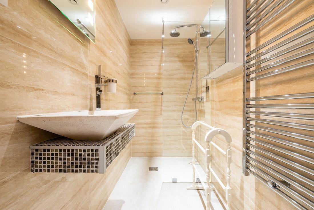 Beige modern bathroom with shower at La Ferme de Margot luxury chalet in Morzine