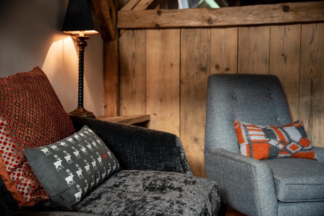 Dark grey couch and orange pillow at La Ferme de Margot luxury chalet in Morzine