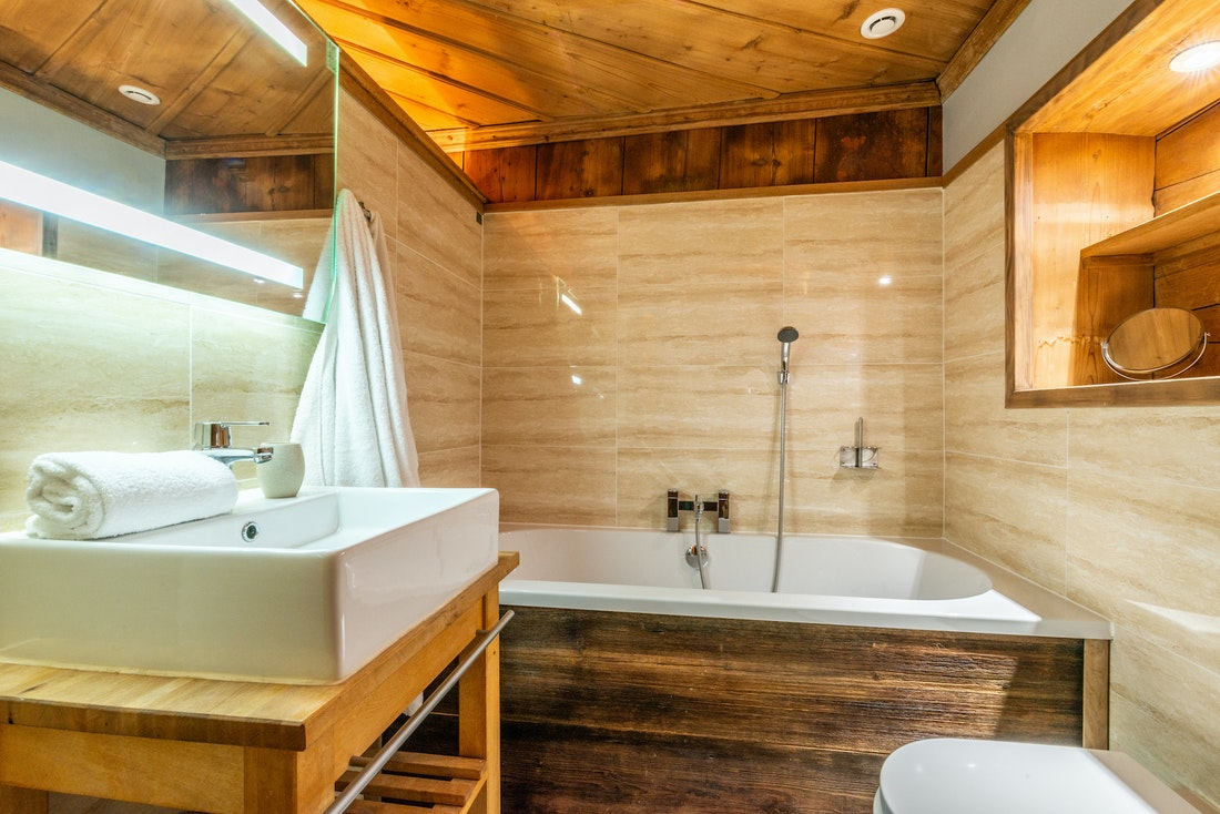 Traditional bathroom with bathtub at La Ferme de Margot luxury chalet in Morzine