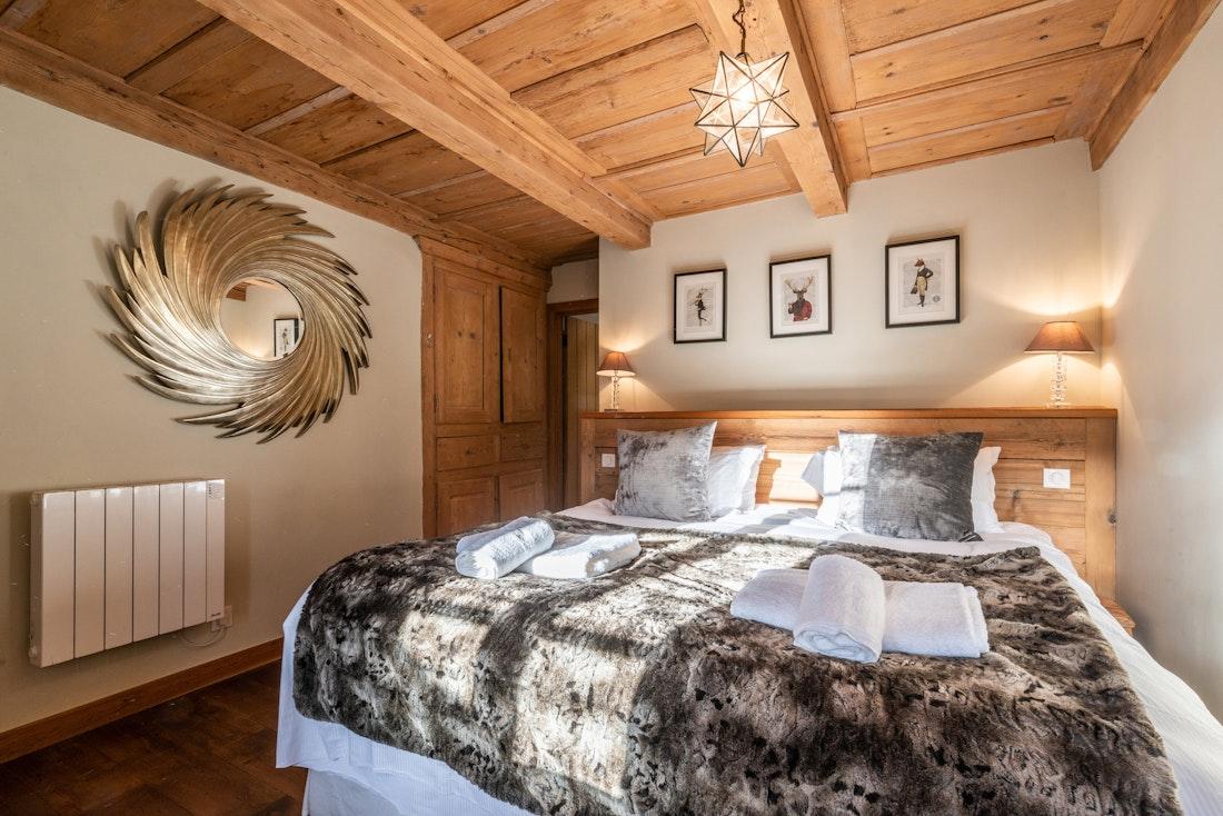 Double bedroom with faux-fur blanket at La Ferme de Margot luxury chalet in Morzine