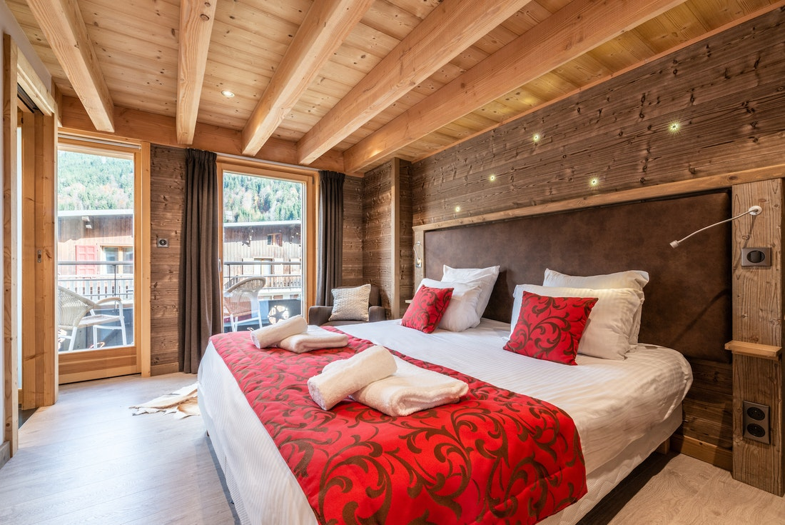 Double bedroom with red sheet details at Etoile accommodation in Morzine