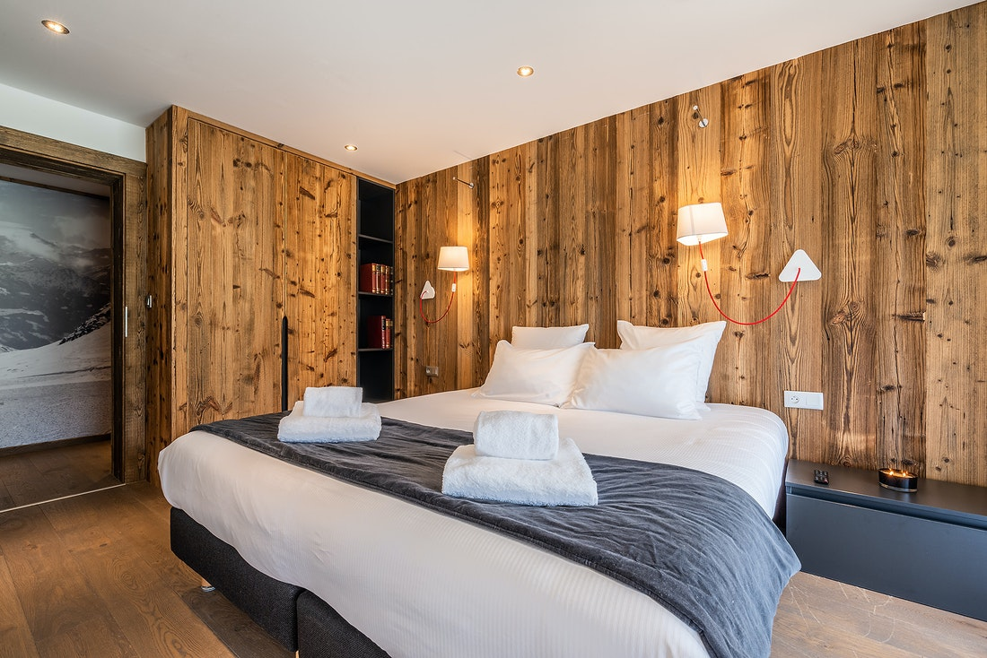 Double bedroom with wooden walls at Le Rouge luxury chalet in Morzine