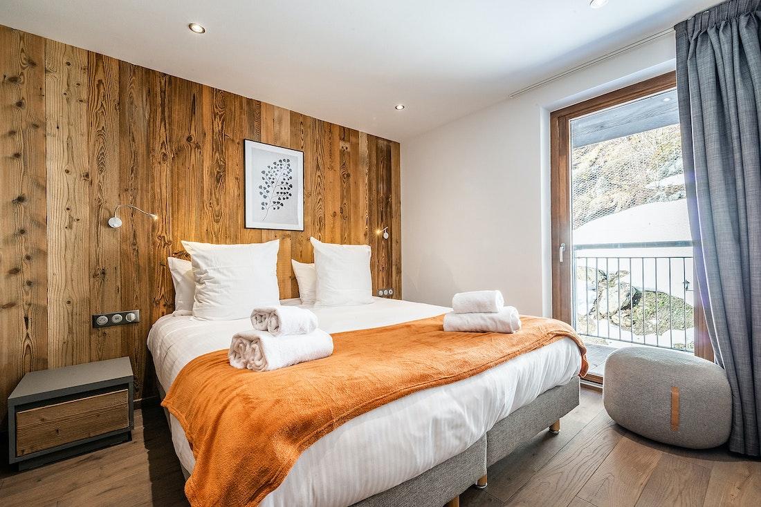 Cosy double bedroom with orange throw at Ravanel luxury accommodation in Chamonix
